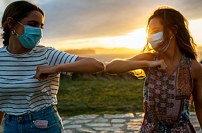 Young women in protective face masks elbow bumping against sky during COVID-19 - p300m2221613 by Marco Govel