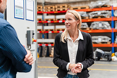 Smiling businesswoman with hands clasped discussing with male colleague in factory - p300m2240132 by Daniel Ingold