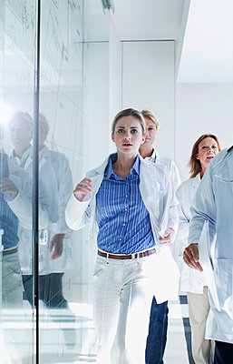 Female and male doctors running down a corridor, Cape Town, South Africa - p300m2281415 von LOUIS CHRISTIAN
