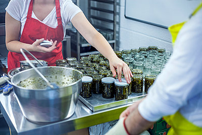 Woman putting lids on jars of jam in industrial kitchen, mid section - p429m2023243 by Seb Oliver