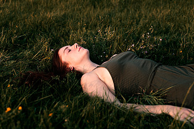Young woman lying on the meadow - p947m2273186 by Cristopher Civitillo