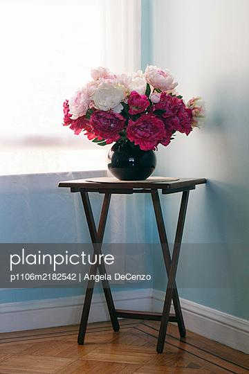 Plastic peonies on corner table at the window - p1106m2182542 by Angela DeCenzo