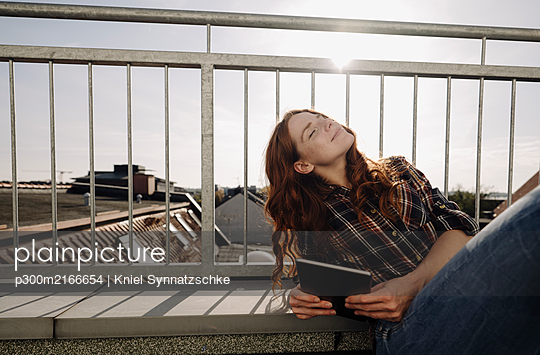 Redheaded woman with tablet relaxing on rooftop terrace - p300m2166654 von Kniel Synnatzschke