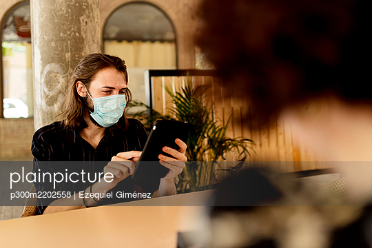 Young man wearing mask while sitting and using digital tablet in restaurant - p300m2202558 by Ezequiel Giménez