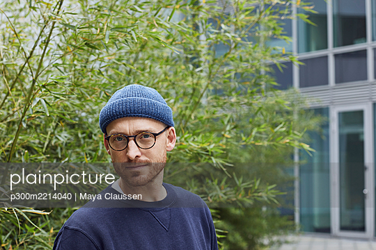 Thoughtful man standing against green leaves - p300m2214040 by Maya Claussen