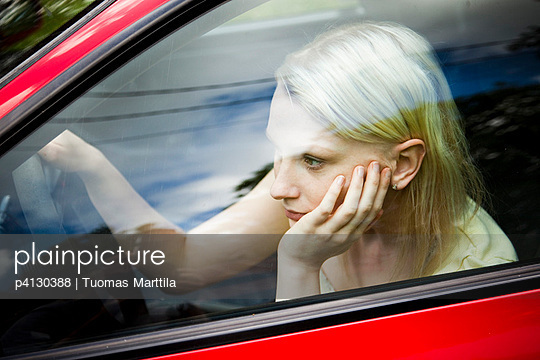 Young woman sitting in her car - p4130388 by Tuomas Marttila