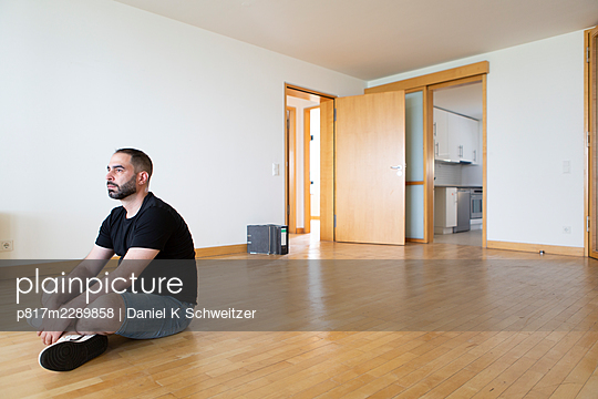 Man with full beard sitting in empty apartment - p817m2289858 by Daniel K Schweitzer