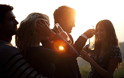 Two men and two women standing outdoors at sunset, holding beer bottles, smiling. - p1100m2214268 by Mint Images