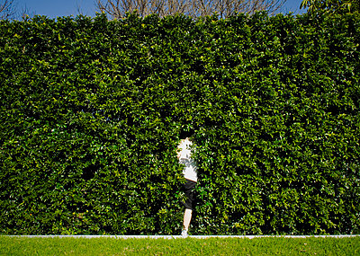 Boy hiding in hedge - p1125m917378 by jonlove