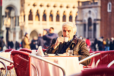 Man with espresso cup in a sidewalk cafe on St. Mark's Square - p1312m2082196 by Axel Killian