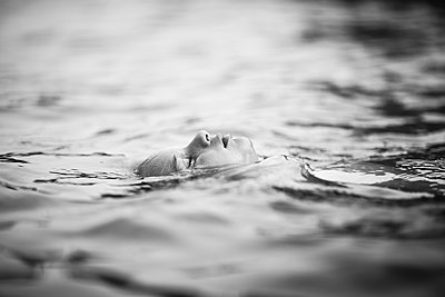 Boy is floating on the water with closed eyes - p1635m2237758 by Amanda Witt