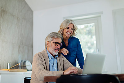 Mature man with wife using laptop on kitchen table at home - p300m2160675 by Sofie Delauw