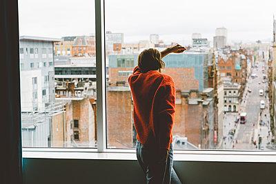 Frau steht nachdenklich am Fenster - p432m2087092 von mia takahara
