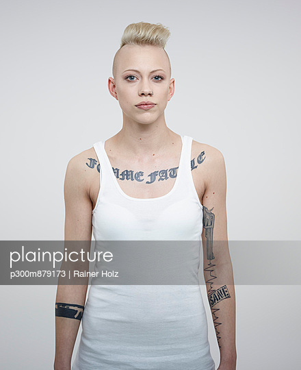 Portrait of young woman with tattoos against white background - p300m879173 by Rainer Holz