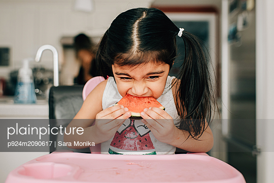 Girl in high chair eating water melon - p924m2090617 by Sara Monika