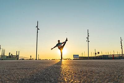 Acrobat doing movement training in city at sunrise - p300m2012262 von VITTA GALLERY