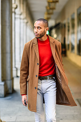Fashionable young man wearing red pullover and brown coat walking along arcade - p300m2070488 von Javier Sánchez Mingorance