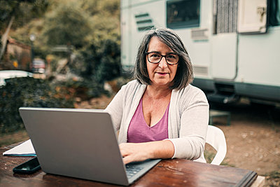 Camping woman using laptop sitting at table - p300m2299017 by LUPE RODRIGUEZ