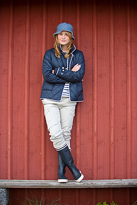 Teenage girl against wooden wall, Vastkusten, Sweden - p312m928620 by Malcolm Hanes