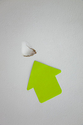 Large green paper arrow pointing to a hole in the wall - p3971186 by Peter Glass