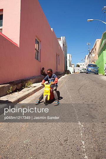 Afrikanischer Junge fährt auf Roller - p045m1217349 von Jasmin Sander