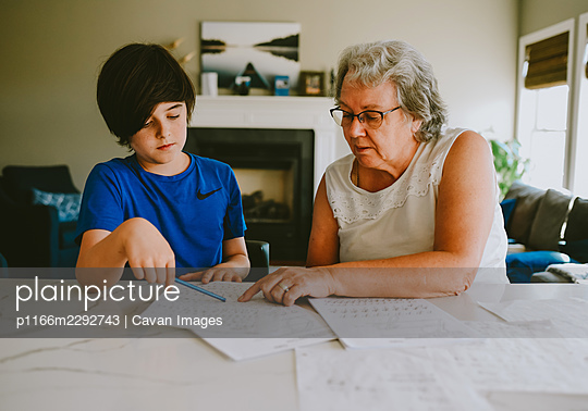 Grandmother helping grandson with writing homework at home. - p1166m2292743 by Cavan Images