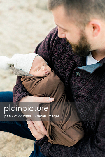 A father holding his newborn sleeping son in his arms - p1166m2292806 by Cavan Images