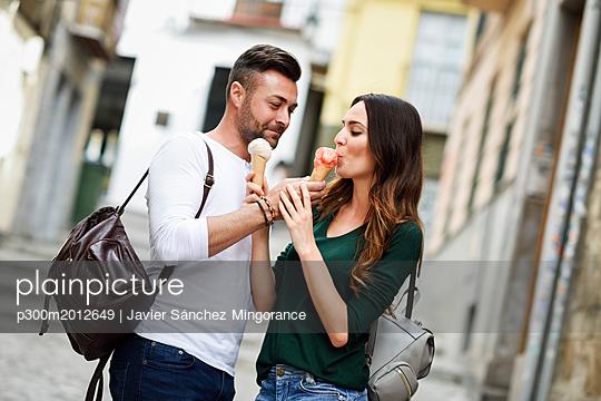 Tourist couple sharing ice cream cones in the city - p300m2012649 von Javier Sánchez Mingorance