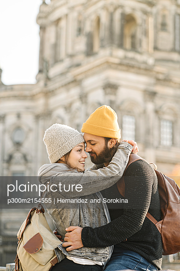 Happy young couple embracing with Berlin Cathedral in background, Berlin, Germany - p300m2154555 by Hernandez and Sorokina