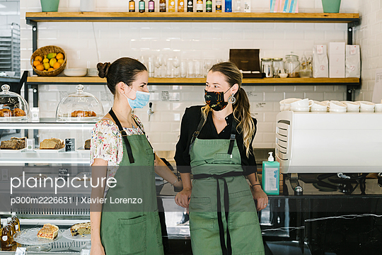 Businesswomen wearing face mask and apron standing by counter at coffee shop - p300m2226631 by Xavier Lorenzo