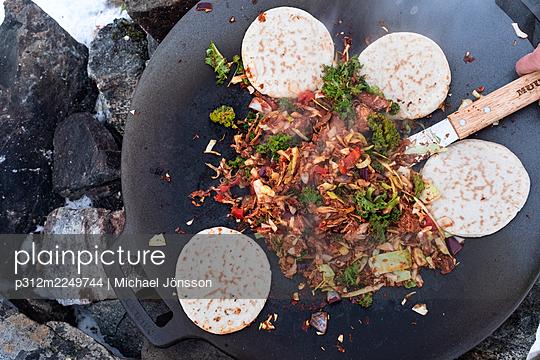 Preparing food over campfire - p312m2249744 by Michael Jönsson