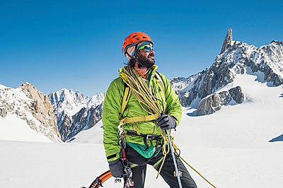 Hiker with climbing equipment standing on snow covered mountain against clear blue sky - p1166m1474111 by Cavan Images