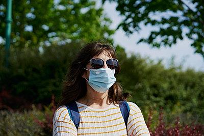 Woman in mask in park - p1166m2201413 by Cavan Images