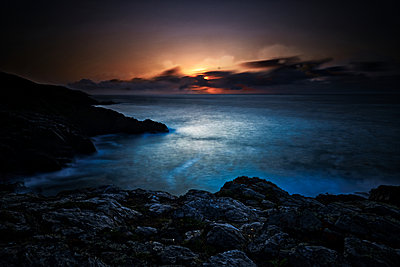 Dramatic Sunset Behind Clouds, Looking Out To Sea, With Headland - p1166m2207928 by Cavan Images