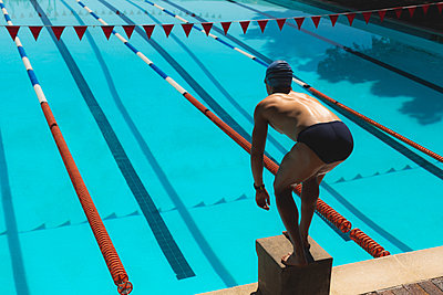 Young male swimmer standing on starting block  - p1315m2091010 by Wavebreak