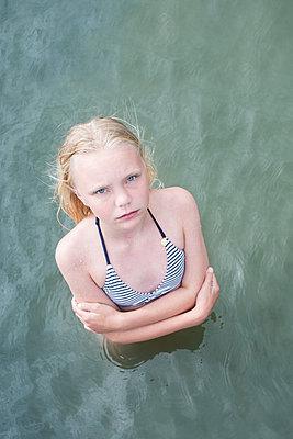 Girl standing in water looking up - p1323m2100721 von Sarah Toure