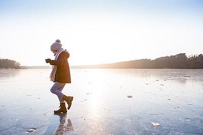 Germany, Brandenburg, Lake Straussee, girl walking on frozen lake - p300m1581753 by Julia Otto