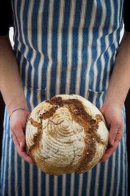 Woman holding homemade sourgough rye bread - p300m1587726 von Larissa Veronesi