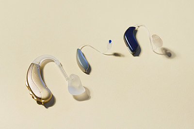 High angle view of various hearing aids on yellow table - p301m1498512 by Halfdark