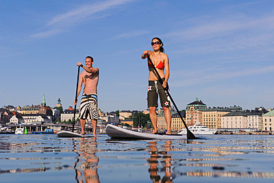 Couple stand up paddle surfing - p31227566f by Hans Berggren