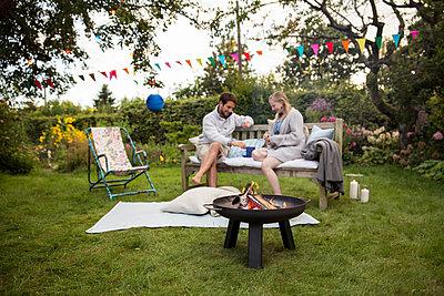 Freunde unterhalten sich auf der Gartenbank  - p788m1165269 von Lisa Krechting