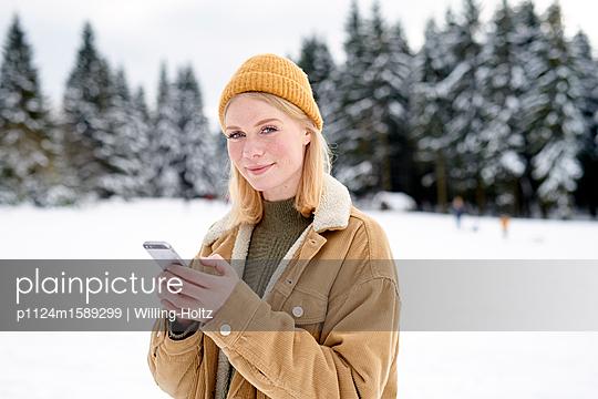 Frau mit Smartphone in verschneiter Landschaft - p1124m1589299 von Willing-Holtz