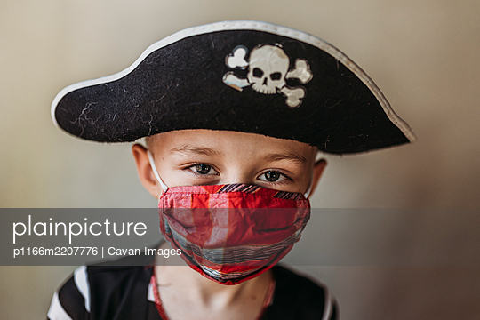 Portrait of school age young boy dressed as pirate with face mask on - p1166m2207776 by Cavan Images
