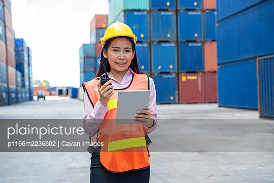 Container worker women in cargo shipping workplace working and c - p1166m2236882 by Cavan Images