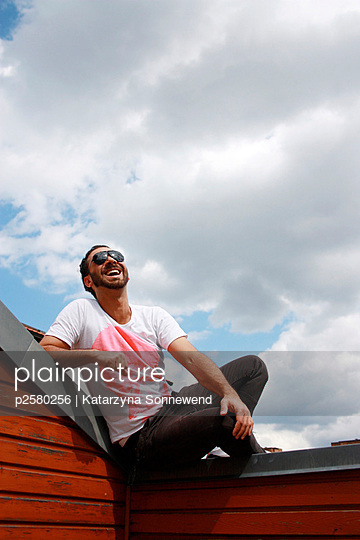 Man sitting on a roof - p2580256 by Katarzyna Sonnewend