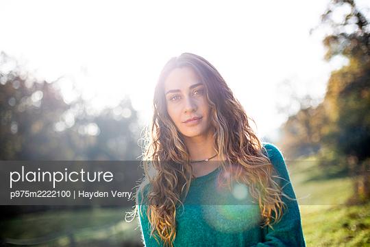 Junge Frau mit langen Haaren in einem Park - p975m2222100 von Hayden Verry