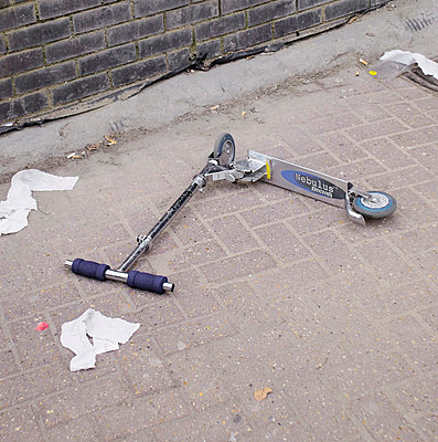 Abandoned child's scooter on pavement with litter - p1072m829353 by Neville Mountford-Hoare