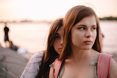 Portrait of lesbian couple sitting by river at sunset during summer - p1166m2212497 by Cavan Images