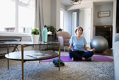 Serene senior woman meditating on yoga mat in living room - p1192m2109857 by Hero Images