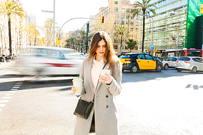 Spain, Barcelona, young woman with coffee to go standing at roadside looking at cell phone - p300m1587847 by Valentina Barreto